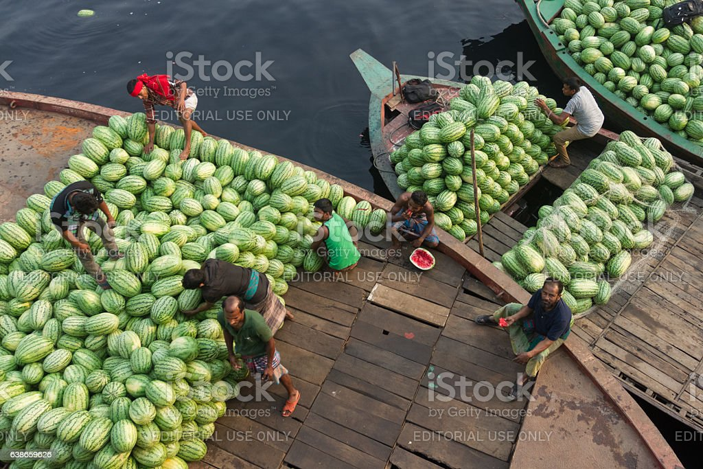 People are unloading watermelons from ferry to small boat. stock photo