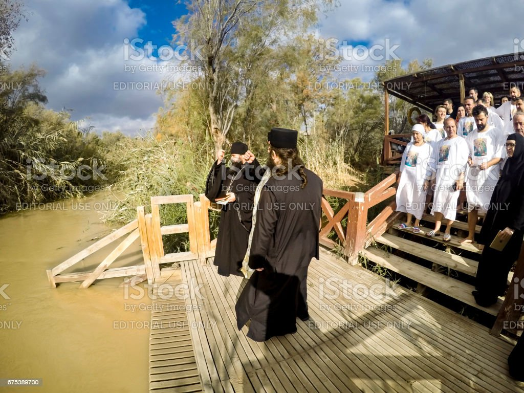 YERICHO, ISRAEL - 20 FEB, 2017: People are waiting to be baptized by water during a baptism ritual at Qasr el Yahud near Yericho on the Jordan river stock photo