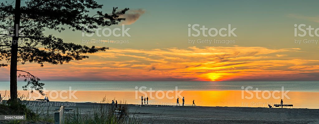 People are walking at sandy beach of Jurmala during sunset stock photo