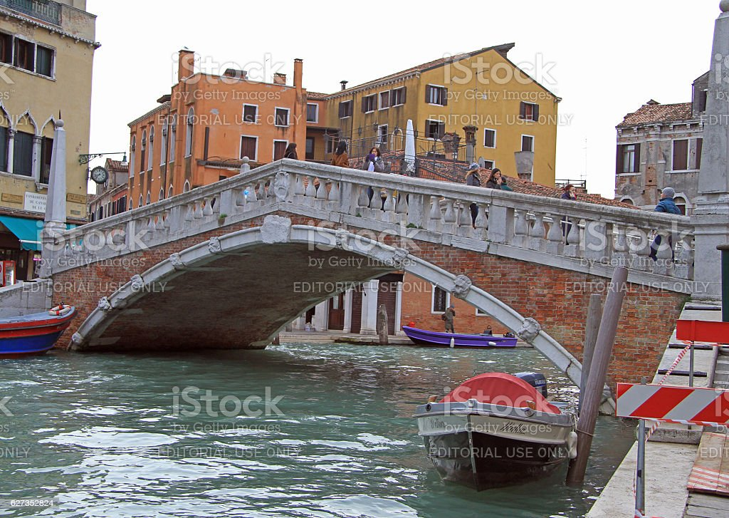 people are walking by the picteresque bridge in Venice, Italy stock photo