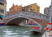 people are walking by the picteresque bridge in Venice, Italy