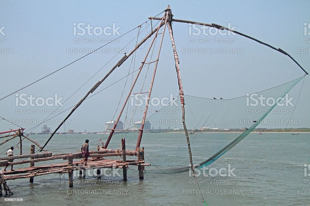 People are walking near chinese fishing nets in Kochi stock photo