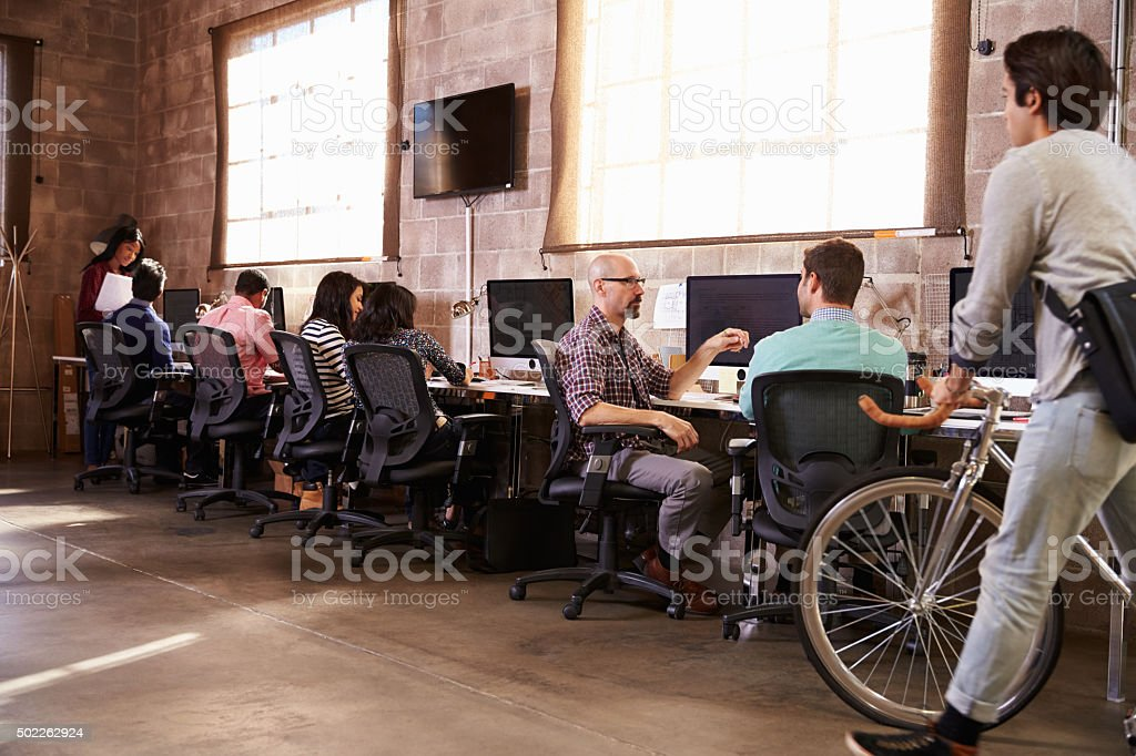 People Arriving For Work In Modern Design Office stock photo