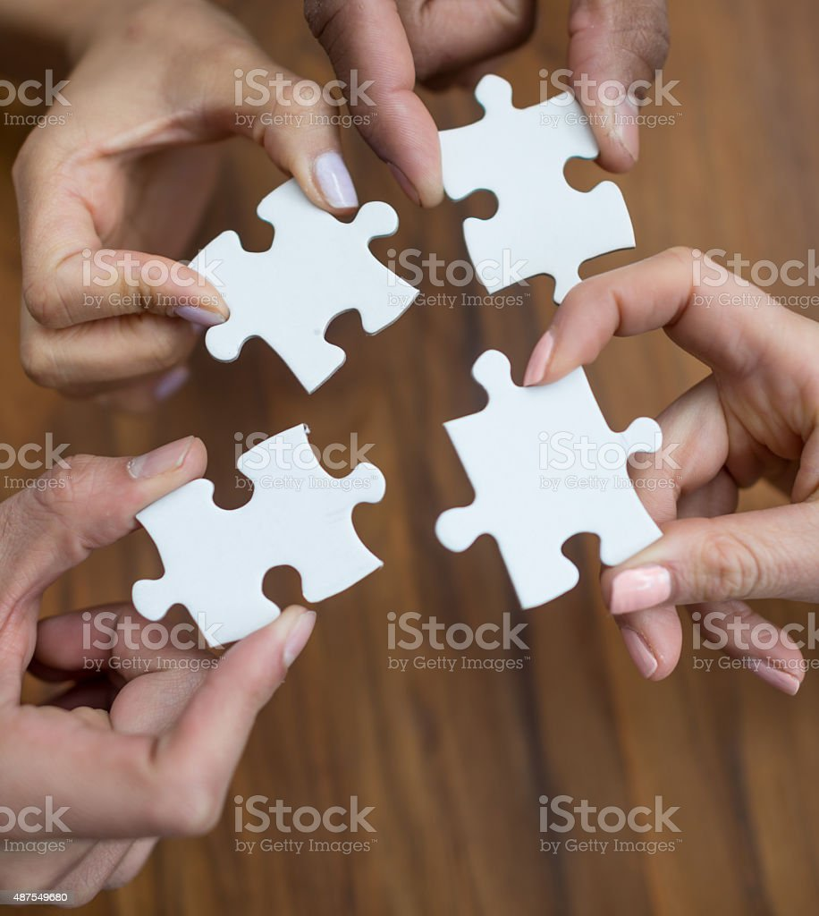 People assembling pieces of a puzzle stock photo