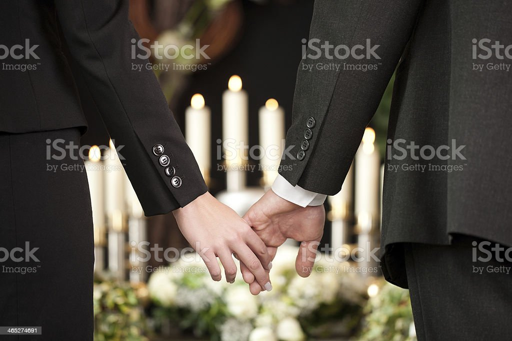 People at a funeral holding hands stock photo
