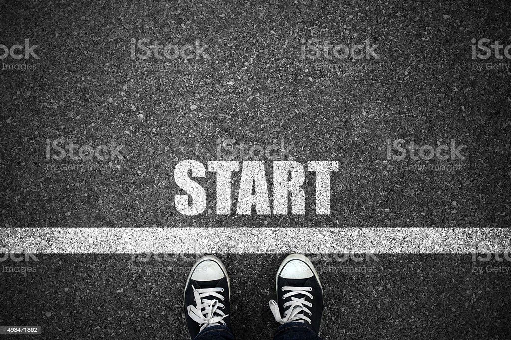 People at a starting line with start text on floor stock photo