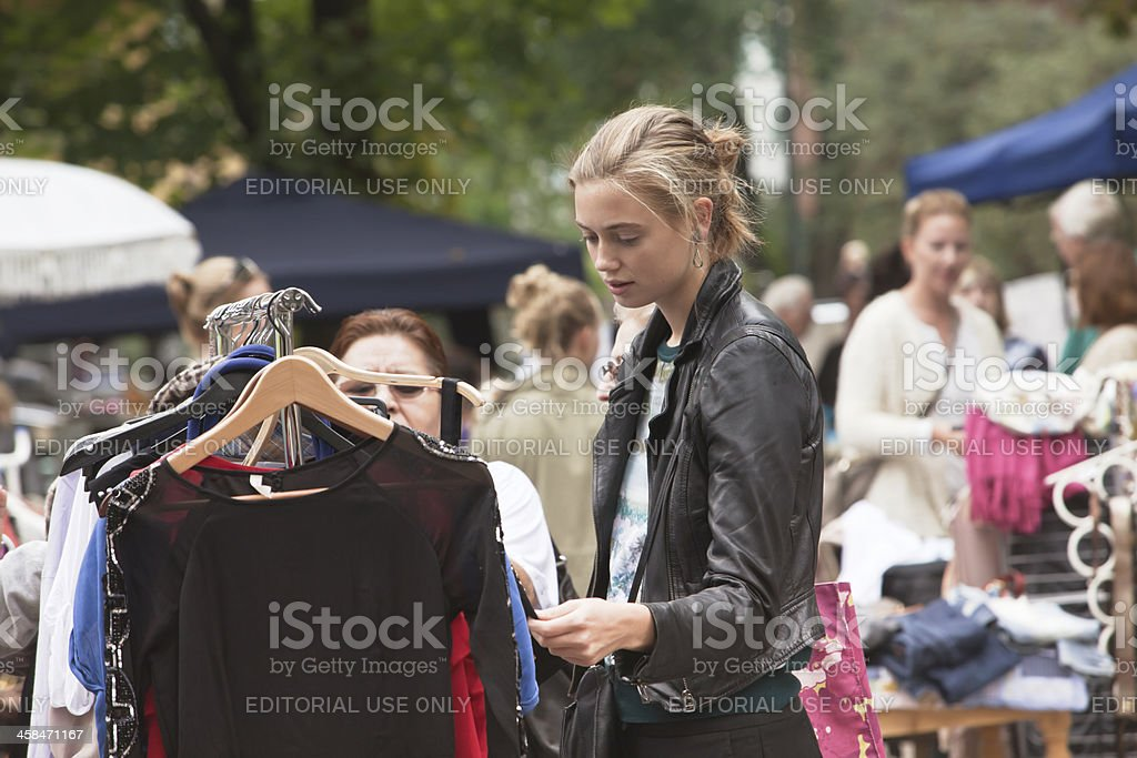 Young woman with hair bun looking at second hand clothes at an...