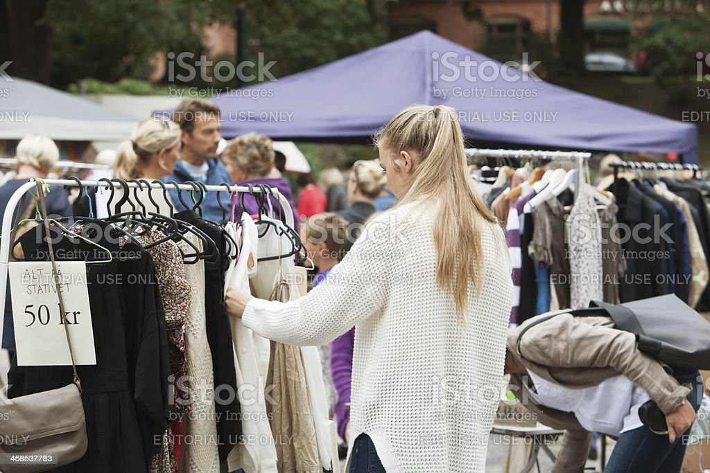 Young woman with pony tail looking at second hand clothes at an...