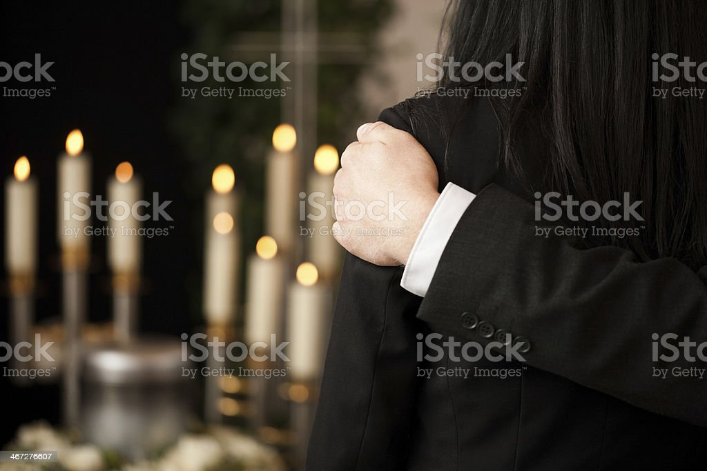 People at funeral consoling each other stock photo
