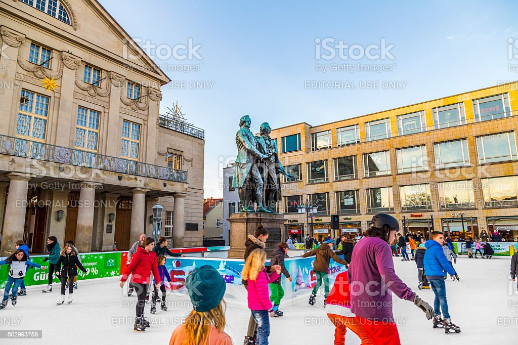 people at Goethe and Schiller monument enjoy ice skatin stock photo