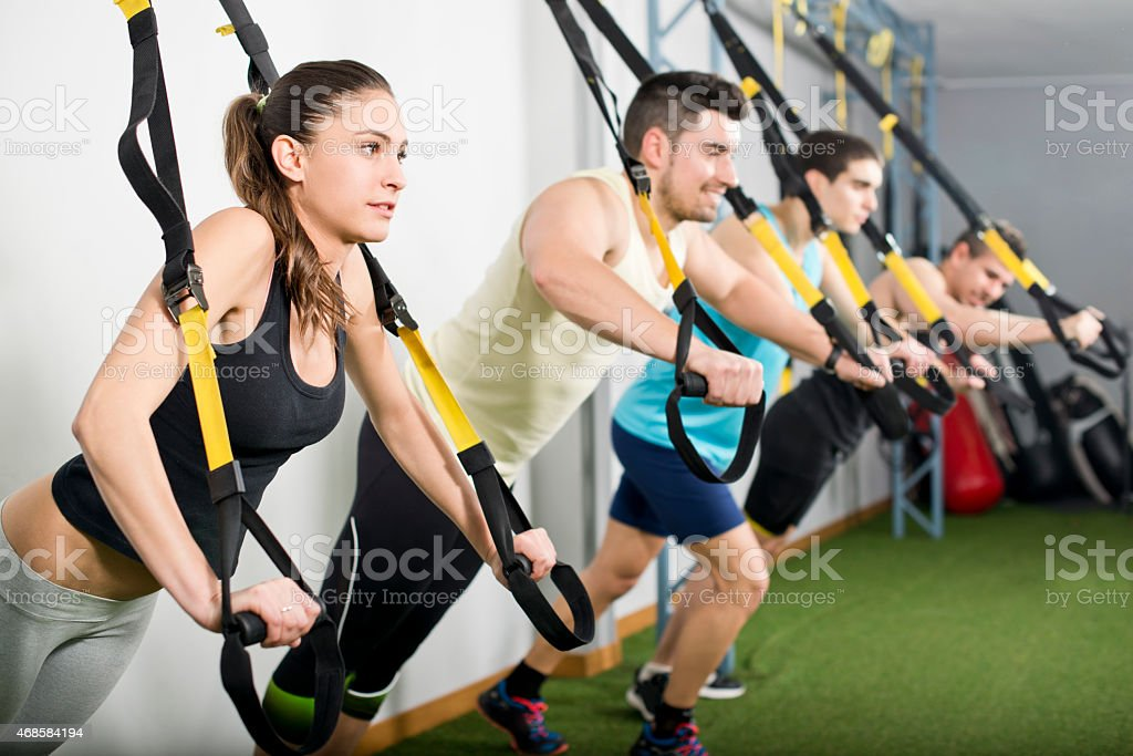 People at gym doing elastic rope exercises stock photo