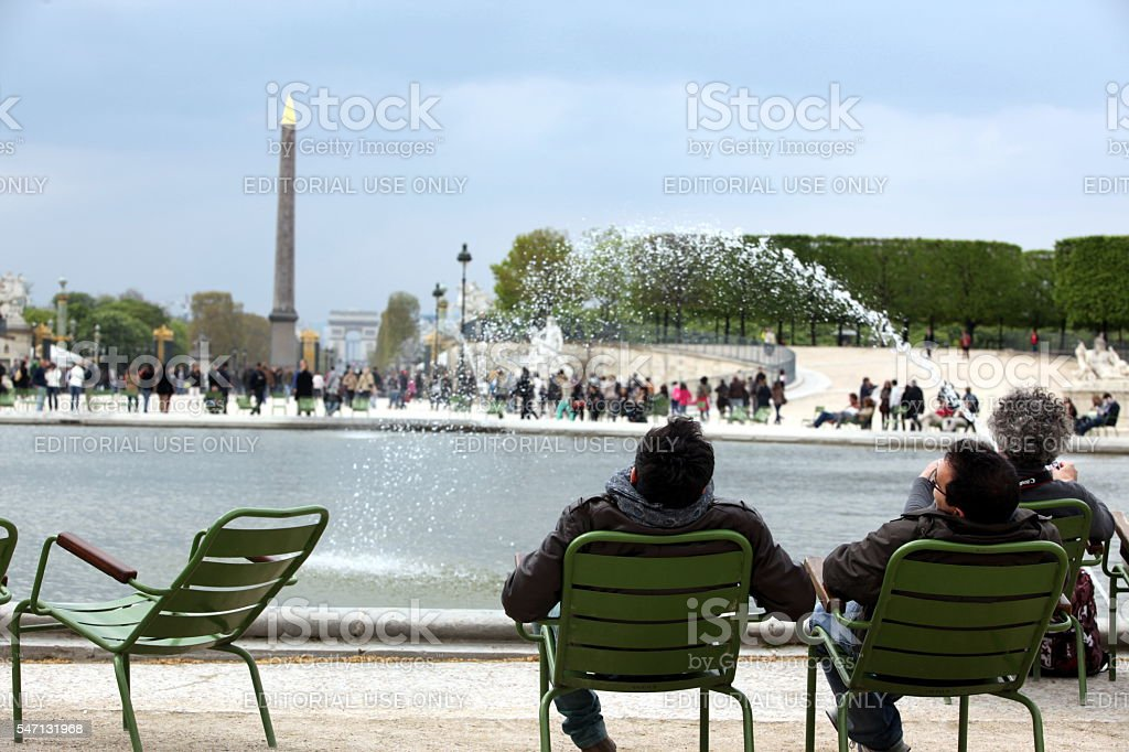 People at Luxor Obelisk and triumphal arch from Tuileries Garden stock photo