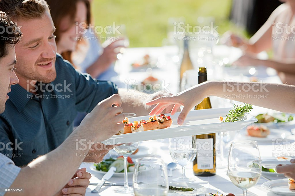 People at outdoor dinner party stock photo