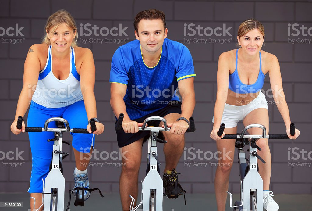 People at the gym doing cardio exercises stock photo