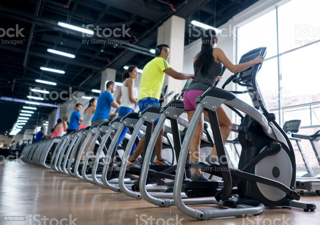 People at the gym exercising on cross trainers stock photo
