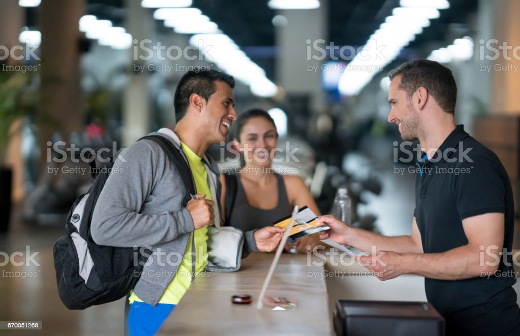 People at the gym talking to the receptionist stock photo
