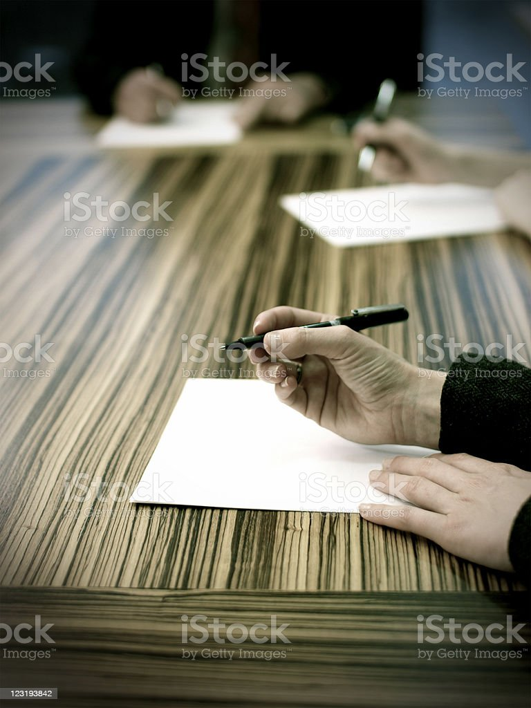 People at the meeting writing notes royalty-free stock photo
