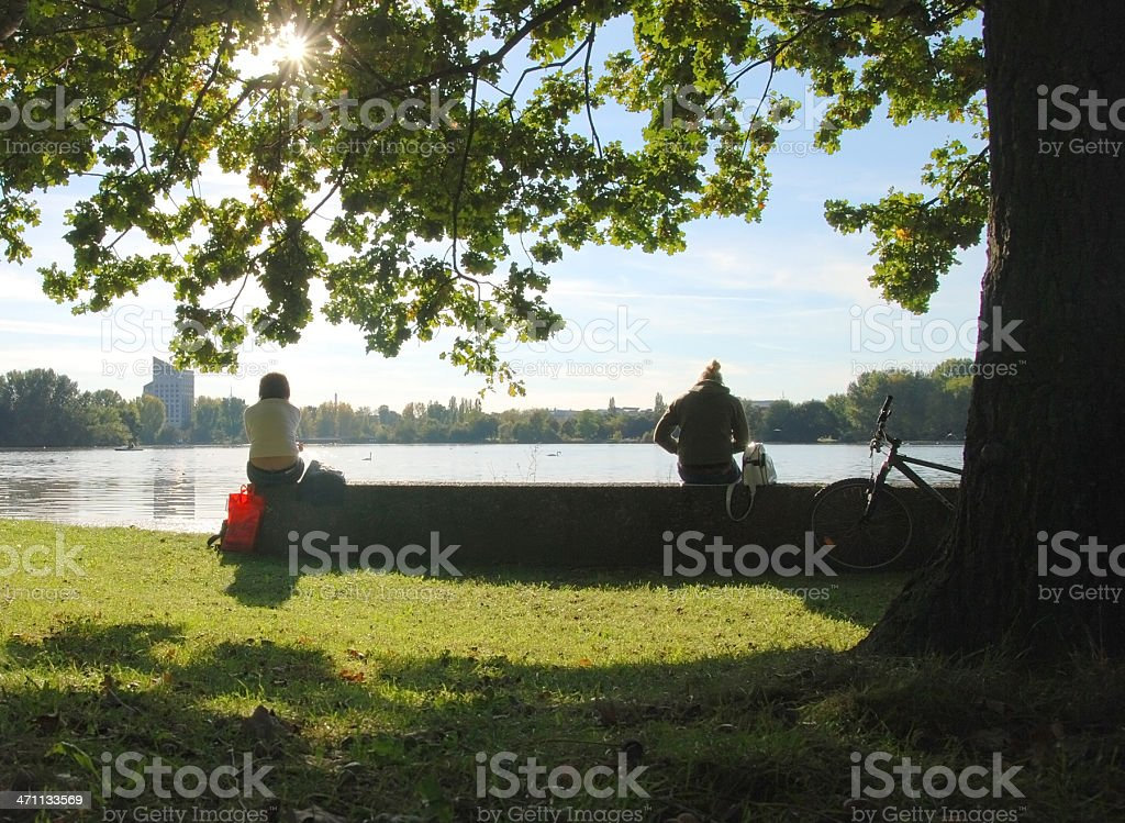 people at waterside in sunset stock photo