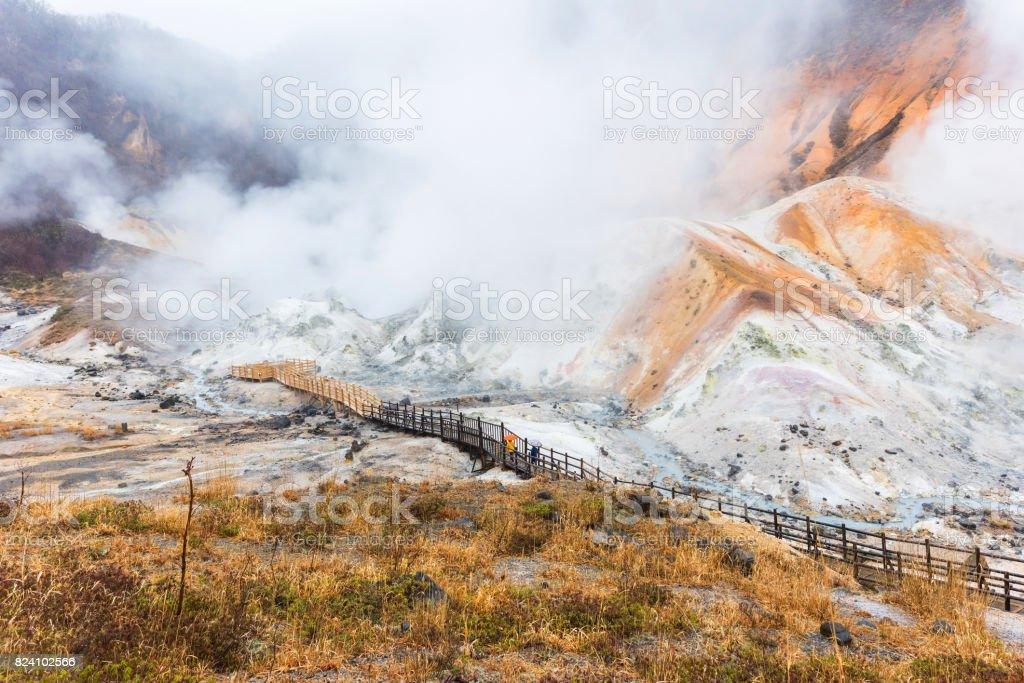 People at wooden trail in Jigokudani hell valley at late evening in Noboribetsu, Hokkaido stock photo