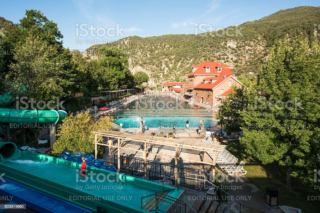 People bathe at public hot springs pool with water slide stock photo