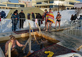 People bathe into cold water of ice-hole on Epiphany day.