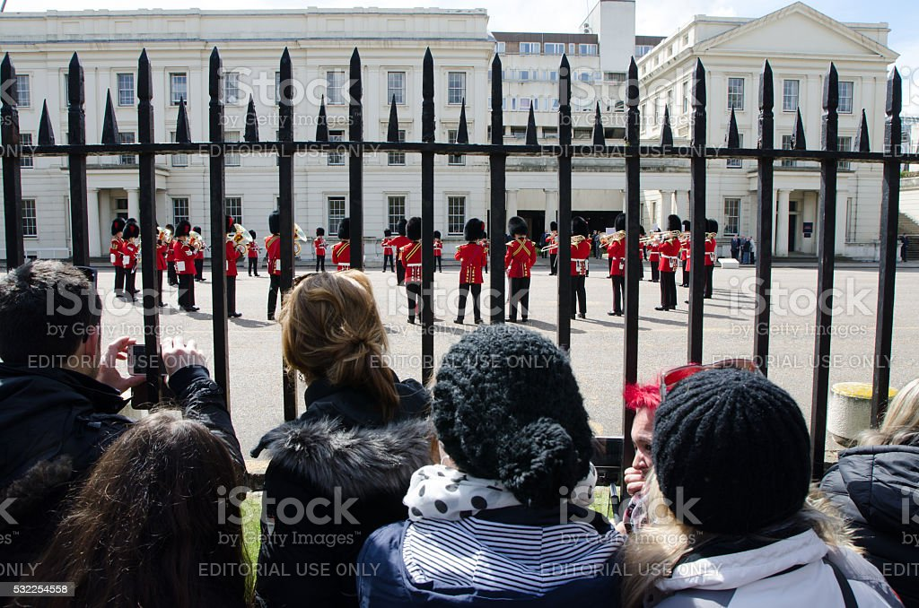 People behind gate watching Royal guards playing music stock photo