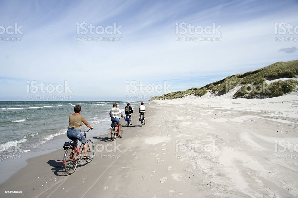 People biking on the edge of the beach royalty-free stock photo