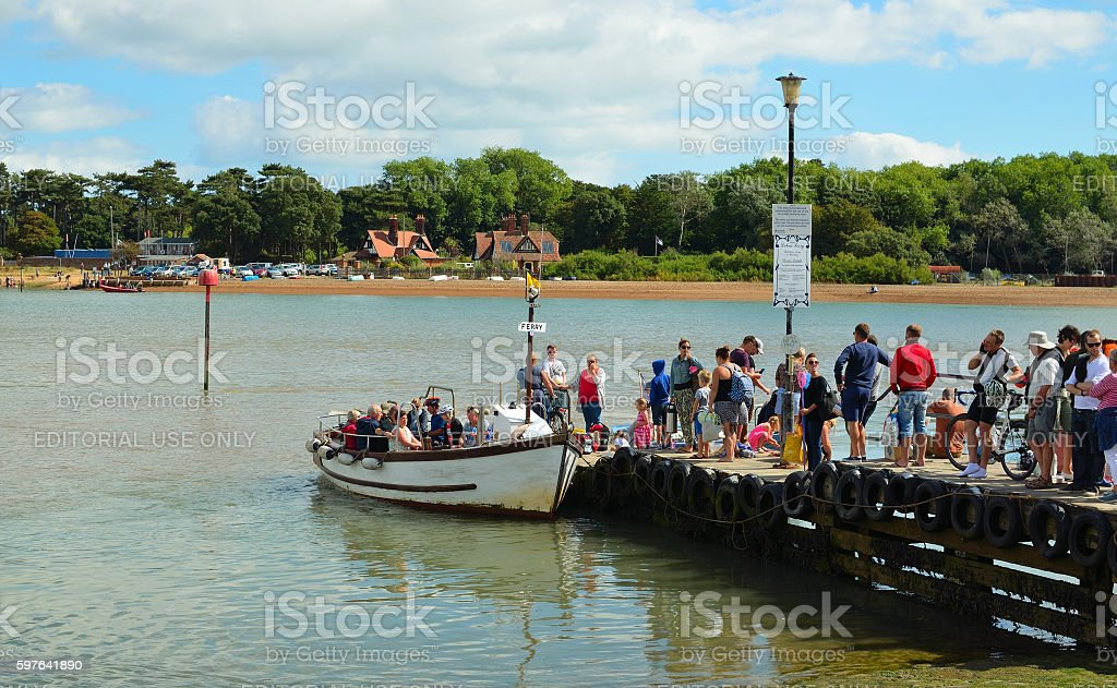People boarding the ferry to cross the river Deben. stock photo