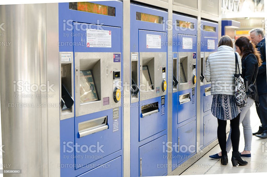 People buying a train ticket at the automatic ticket machine stock photo