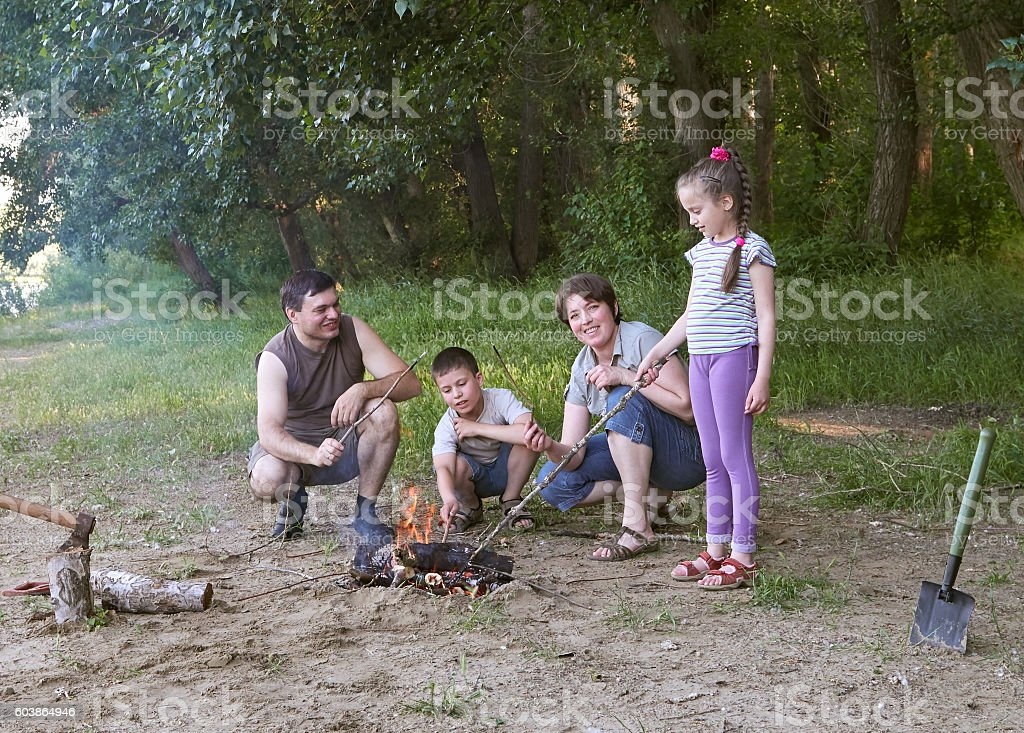 people camping in forest, family active in nature, kindle fire stock photo