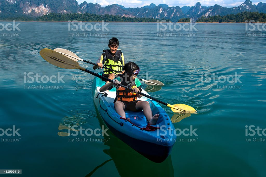 People canoeing on scenic lake in summer, THAILAND stock photo