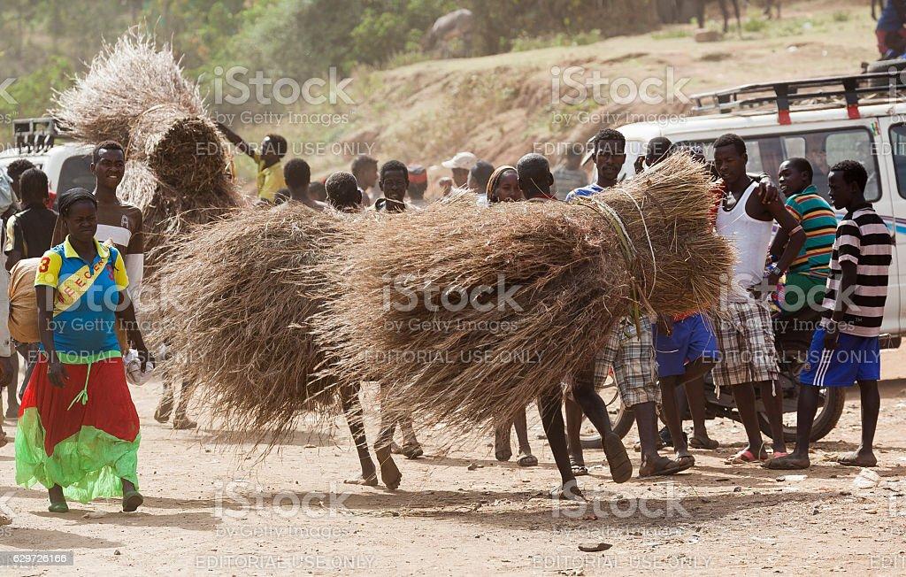 People carry twigs at village market. Bonata. Omo Valley. Ethiopia stock photo