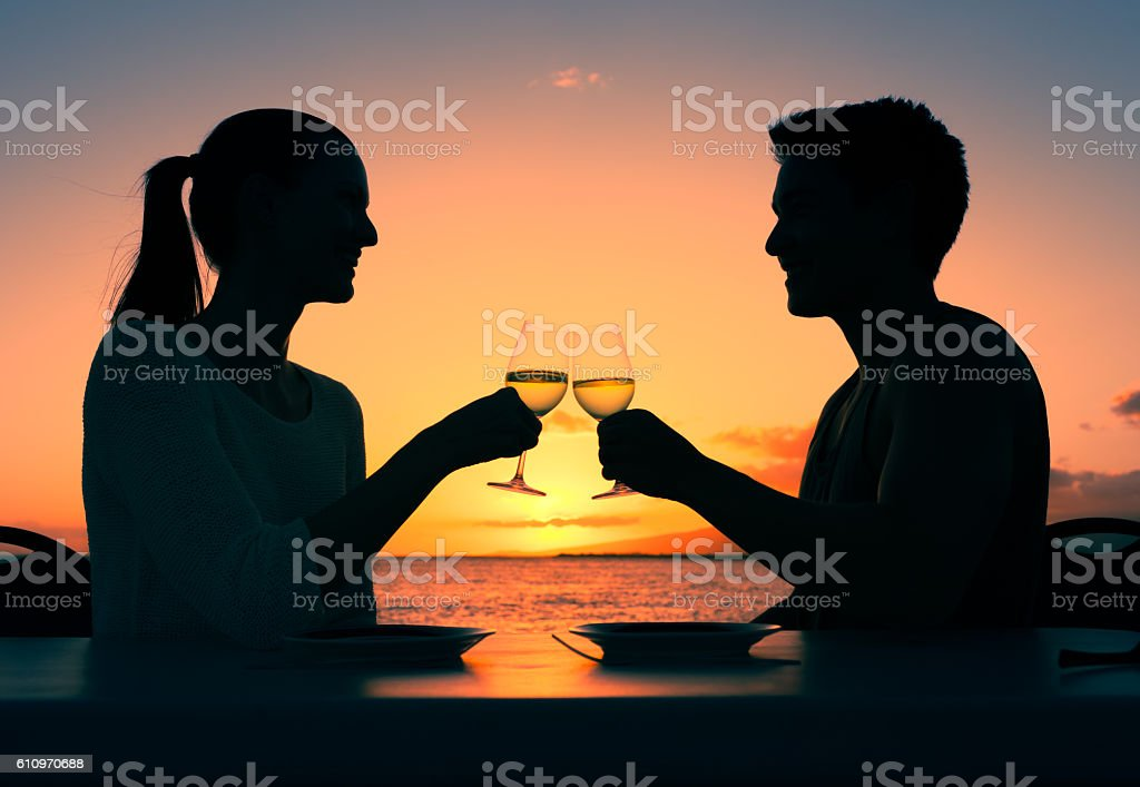 People celebrating drinking wine in a romantic setting. stock photo