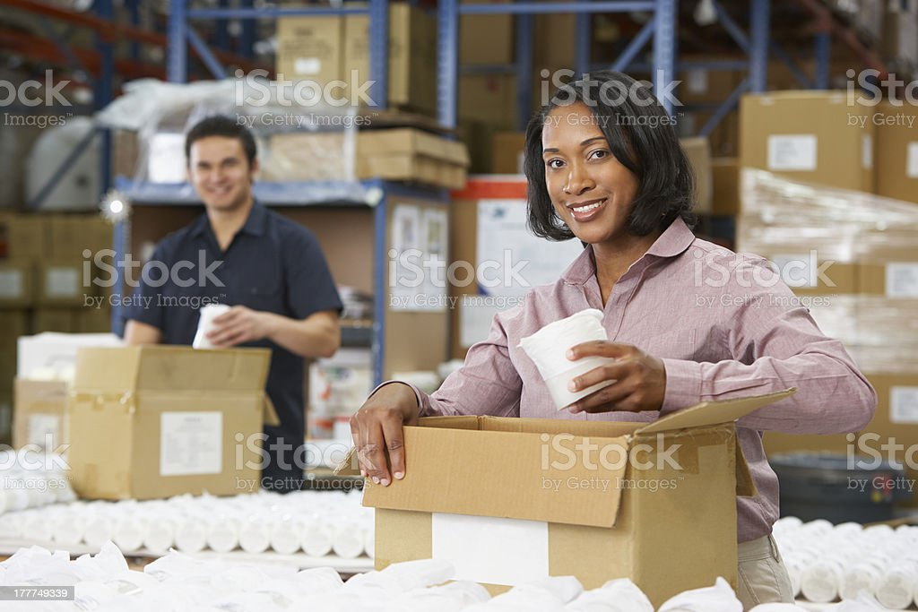 People checking boxes of products at work stock photo