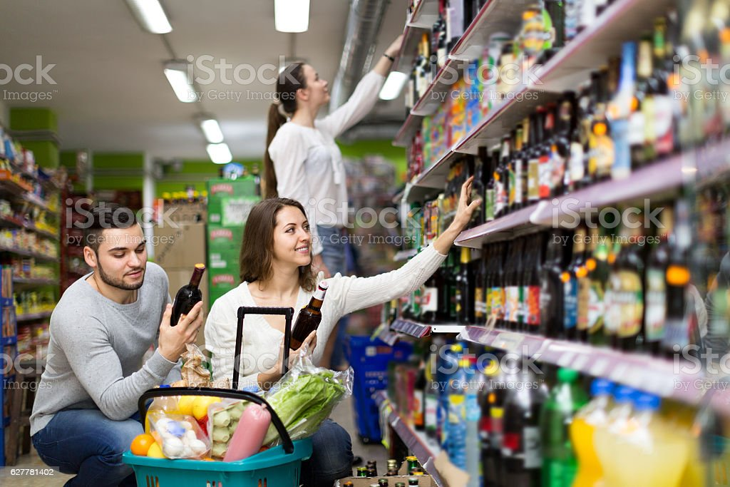 People choosing spirits in hypermarket stock photo