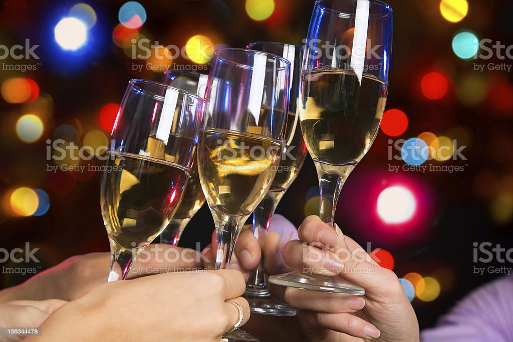 People clanking champagne glasses together with lights stock photo