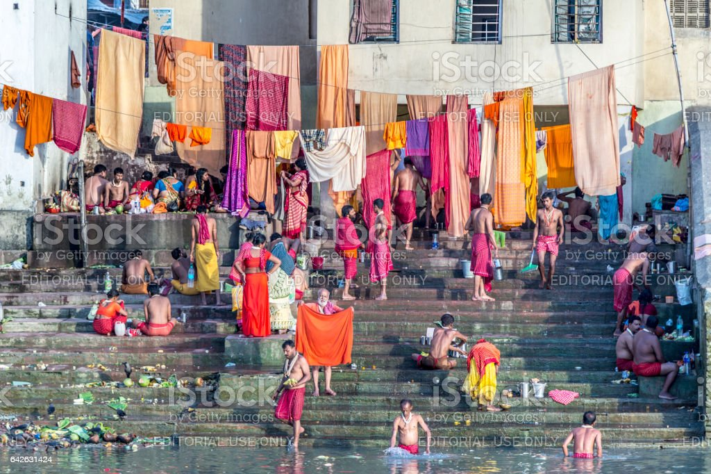 people cleaning clothes and washing in the river Ganges stock photo