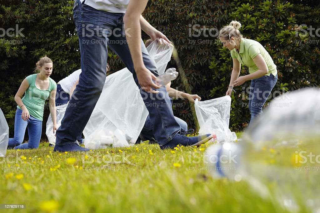 People cleaning up litter on grass stock photo