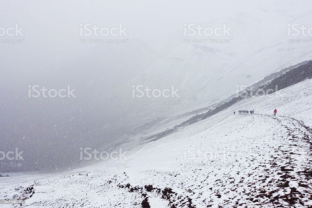 people climb snowy mountain pass white out stock photo