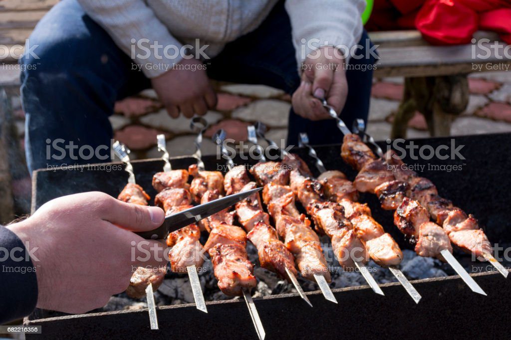 people cook the meat on the skewers on the grill stock photo