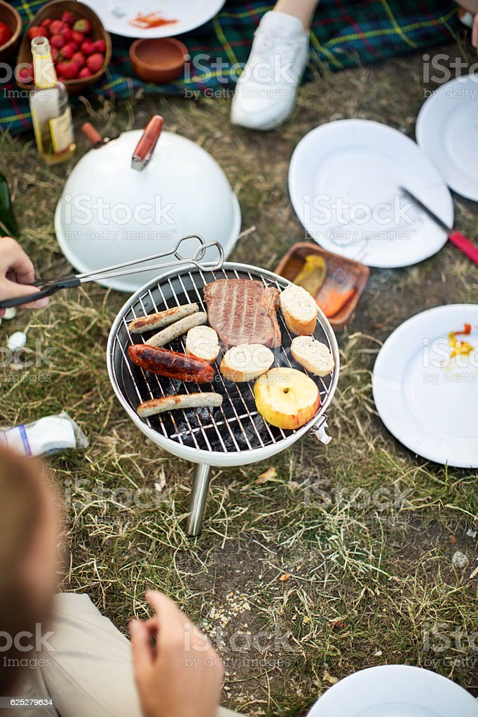 People cooking on barbeque grill outdoors stock photo