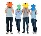 People Covering Face With Puzzle Pieces