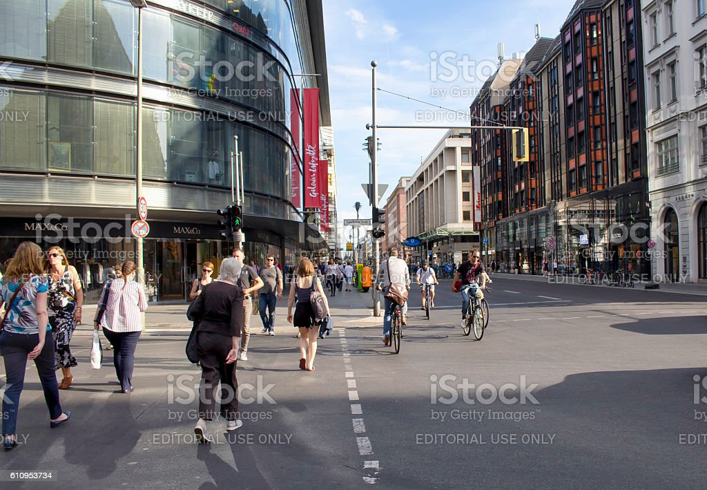 People cross the street and some people ride bicycles stock photo