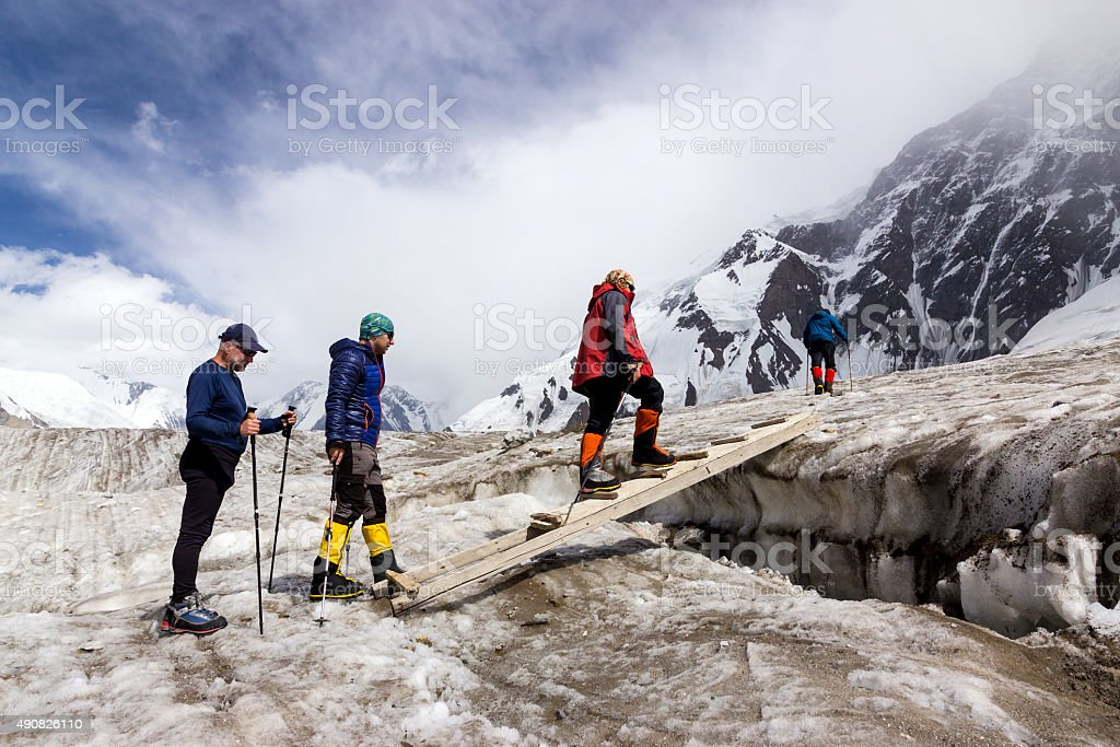 People Crossing Glacier Crevasse on Wood Shaky Footbridge stock photo