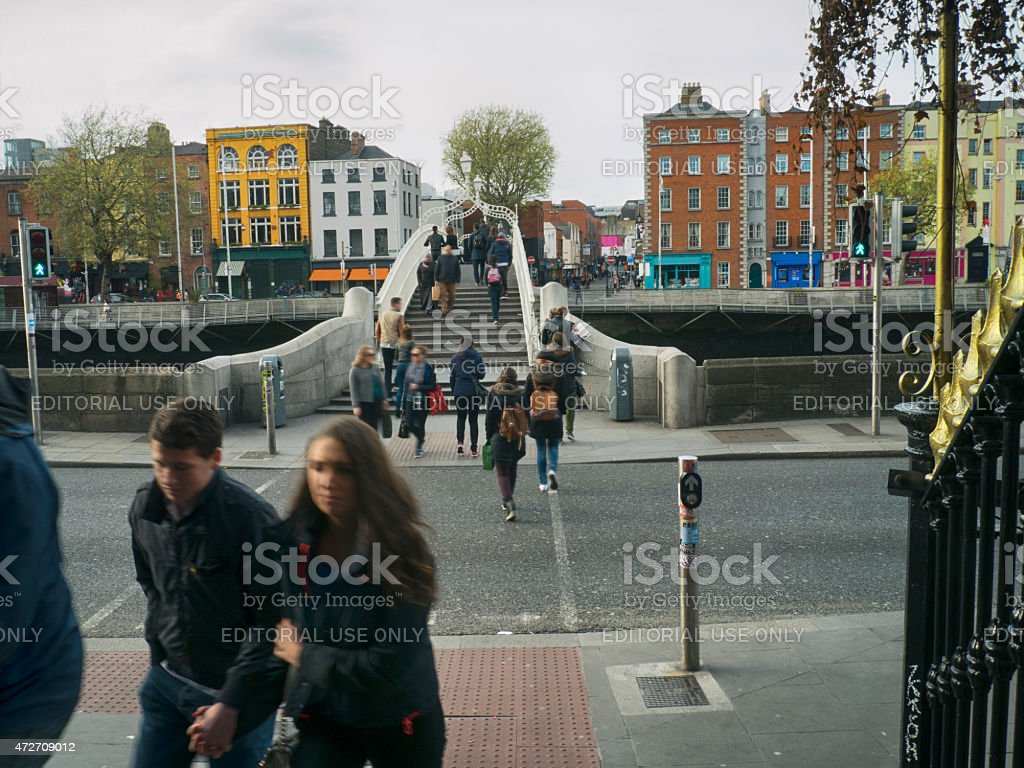 People crossing Ha'penny bridge in Dublin Ireland over river liffey stock photo