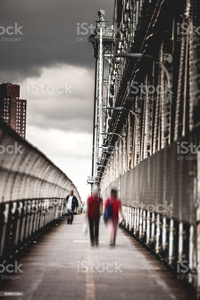 People crossing Manhattan Bridge in New York City stock photo