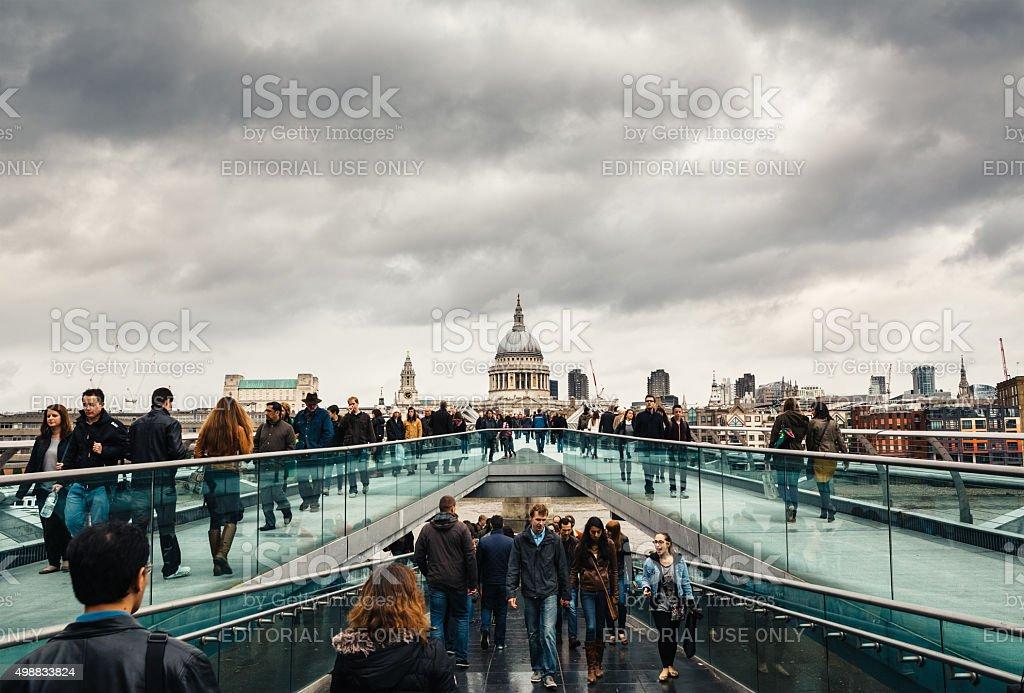 People Crossing Millenium Bridge In London stock photo