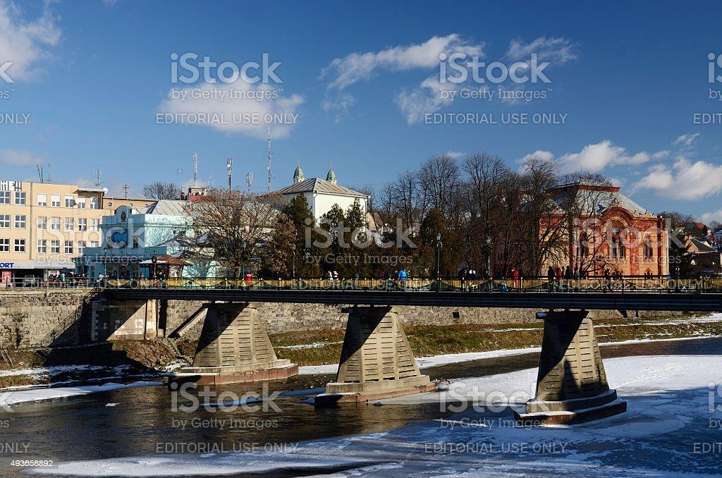 People crossing old pedestrian bridge over Uzh river,Uzhgorod,Ukraine stock photo