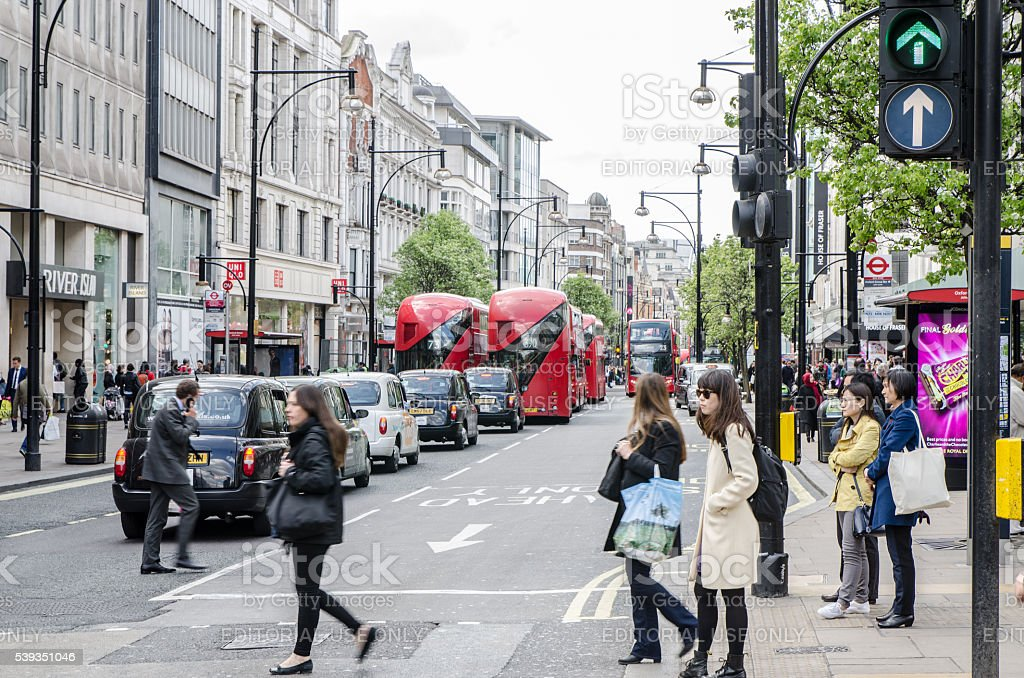 People crossing the street whit cars and double decker buses during...