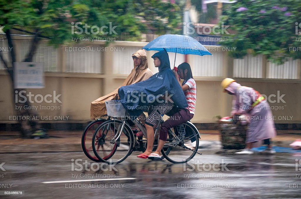 People Cycling In Heavy Rain stock photo